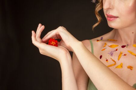 A woman is holding a flower in the palm of her hand.