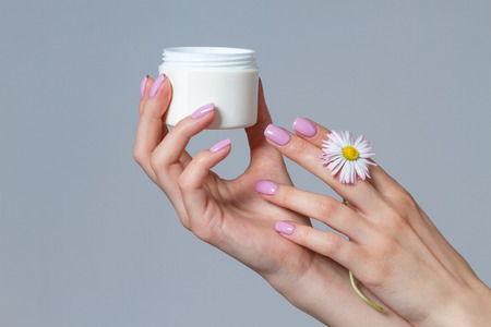 Well-groomed womens hands with a jar of cream. Stock Photo