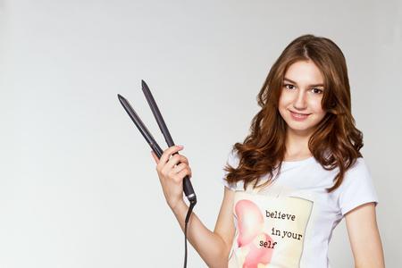 Eine niedliche Frau mit einem Haar Curling-Tool.
