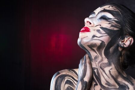 The painted woman with black smears with red lipstick on her lips.