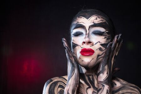 A painted woman with black paint is experiencing emotions.