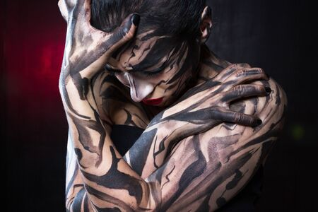 The painted woman with black paint tightly closes her hands and digs her fingers in the skin.
