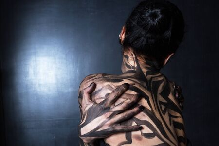 A woman painted with black paint.