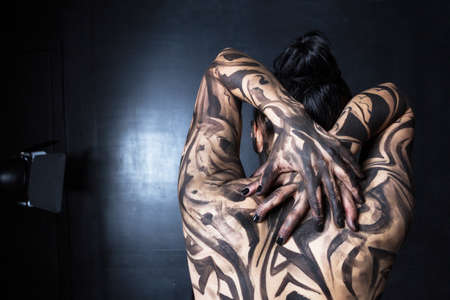 The hands and back of the woman are painted with black strokes.