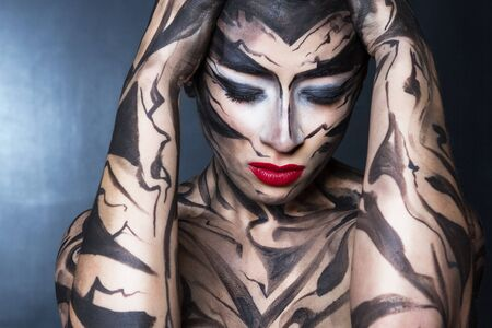 A painted woman with black paint with red lips.