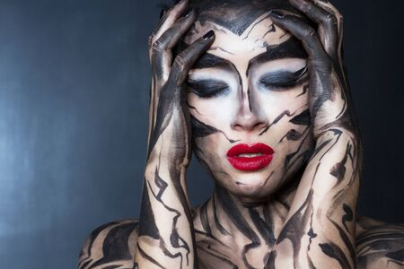 A woman with a painted body and face experiences an emotion of stress.