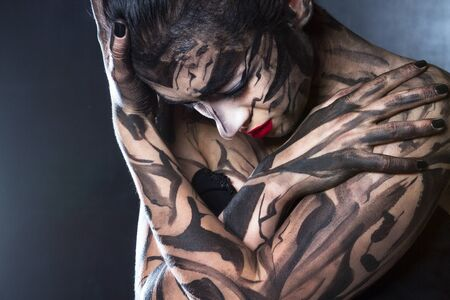 conscience: The painted woman covered herself with her hands and lowered her head down.