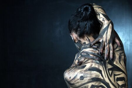The woman is plastered with black paint from the back.