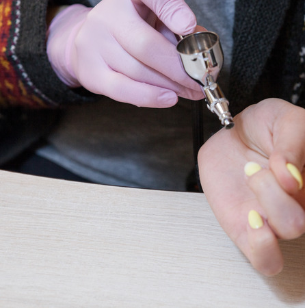 The master does the design on the nails with an airbrush. Stock Photo