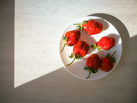 Ripe red strawberries on a white plate.