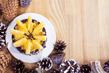 Cake with mandarin slices surrounded by fir cones.