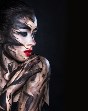 Woman in a gloomy image on a black background. Standard-Bild