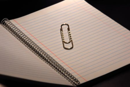 Big paper clip on a paper in black background.