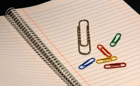 Colorful paper clips and one big paperclip on a lined paper. Stock Photo