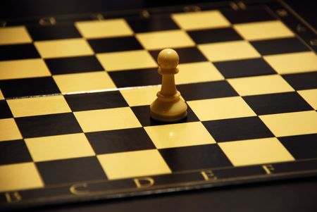The white pawn standing alone on a chess board. Stock Photo