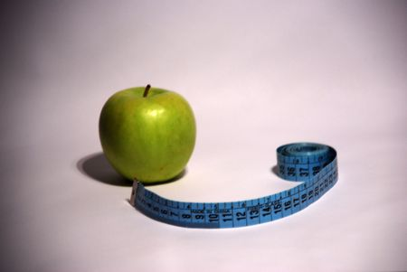 Green apple and a measure tape