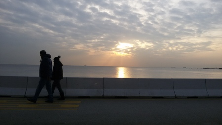sunset on sea with couple walking