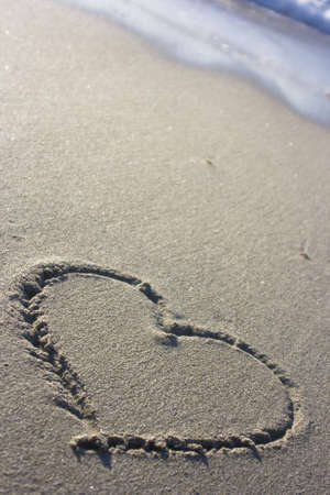 the symbol of a heart in the sand at sunset Stock Photo - 7597800
