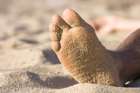 Foot with sand of a man on a beach photo