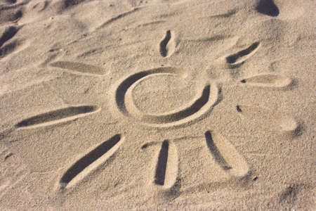 A drawing of a sun in the sand of a beach photo