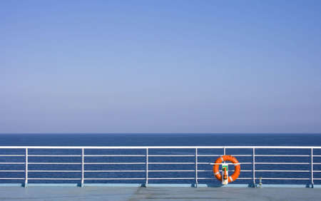 boat deck: Red Lifebuoy in front of the blue sea and the white ship