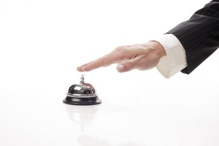 campanas: la mano del hombre de negocios haciendo sonar la campana para llamar a