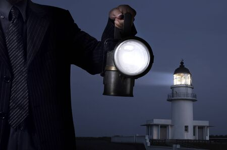 lighthouse at night: business man handing the lamp in darkness  Stock Photo