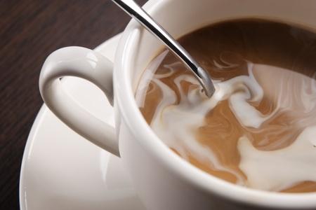 eine Tasse Kaffee mit Sahne wirbeln