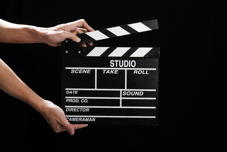 movie camera: hands holding out a clapper in black
