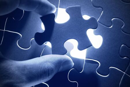 hands placing last piece of a puzzle Stock Photo - 11265401