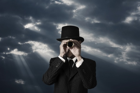 human vision: business man looks through a telescope in darkness