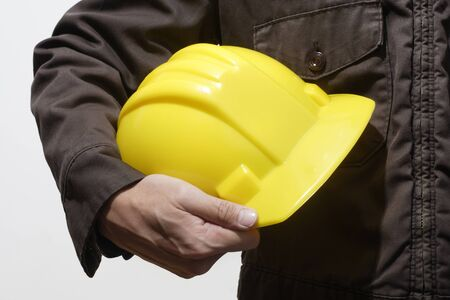 safety equipment: construction worker holding yellow hardhat on white background