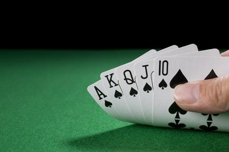 poker table: The Royal Flush on a green poker table against black