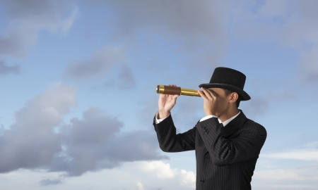 vision concept: business man looks through a telescope