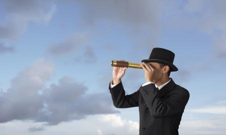 fernrohr: Business-Mann schaut durch ein Teleskop Lizenzfreie Bilder
