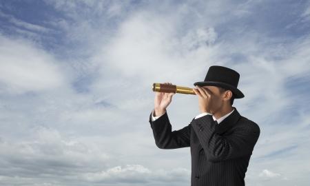 city surveillance: business man looks through a telescope with sky