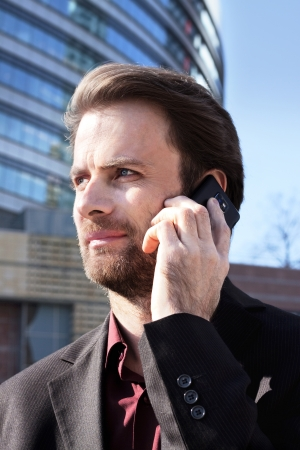 Forty years old businessman standing outside modern office building talking on a mobile phone photo