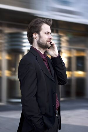 40 years old man: Forty years old businessman standing outside modern office building talking on a mobile phone Stock Photo