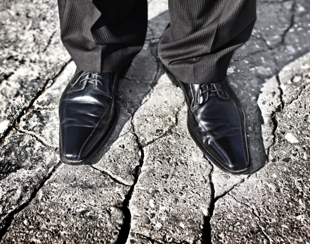 risky situation: Businessman legs standing on a cracked ground - uncertain future, insecure situation or risky investment decision concept