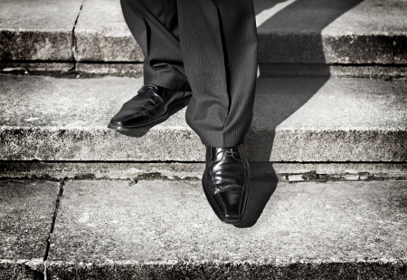 taking a risk: Businessman legs taking step on a lower level on a stairs - bad investment decision concept Stock Photo