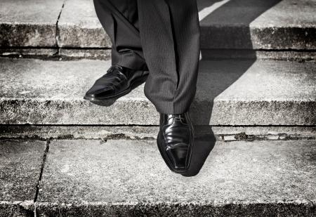Geschäftsmann Beine unter Schritt auf einem niedrigeren Niveau auf einer Treppe - bad Investitionsentscheidung Konzept