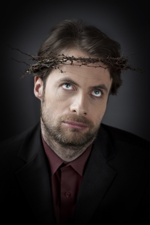 under paid: Contemporary man in a crown of thorns - unhappy, exhausted or frustrated corporation office worker concept