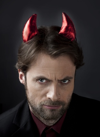 unfair: Man in suit with devil horns  Concept of a nasty, cruel, demanding boss or unfair competition in business