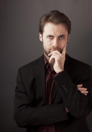 Vierzig Jahre alte Geschäftsmann steht auf einem grauen Hintergrund