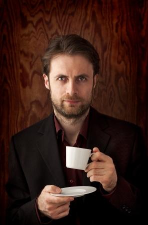 při pohledu na fotoaparát: Čtyřicet let starý business man pití ranní kávy