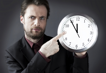 demanding: Forty years old strict demanding boss with a pointing finger on a clock - indicates a deadline hour
