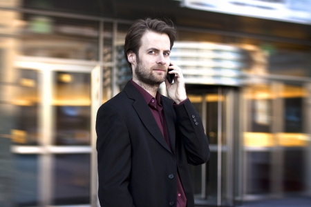 Forty years old businessman standing outside modern office building talking on a mobile phone 스톡 콘텐츠