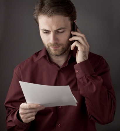 Forty years old office worker reading paper documents during mobile phone conversation - checking terms of agreement 版權商用圖片