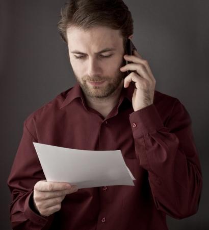 Vierzig Jahre alt Büroangestellter Lesen Papierdokumente während Handygespräche - Überprüfung Bedingungen der Vereinbarung