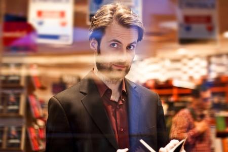 Veertig jaar oude elegante man staande in boekhandel een boek lezen
